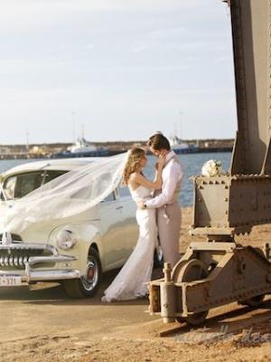 couple kissing at an old car
